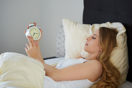 raised viewpoint: attractive woman looking at the clock in the morning Stock Photo