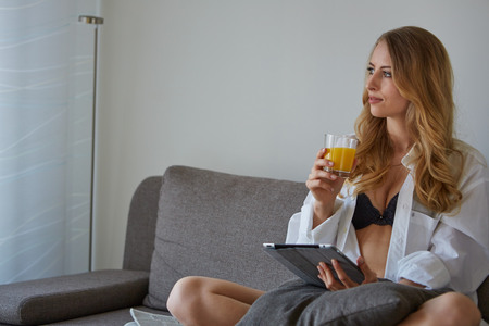 smiling woman with cup of coffee reading magazine at home Stock Photo