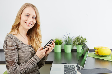 Young woman using tablet computer in an apartment photo