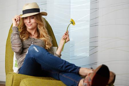 自宅の若い女性が彼女のリビング ルームの読書でリラックス、調色の窓の前でモダンな椅子に座ってください。 写真素材