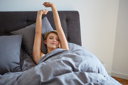 raised viewpoint: attractive woman stretching in the morning and is smiling