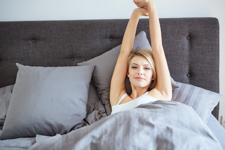 attractive woman stretching in the morning and is smiling photo
