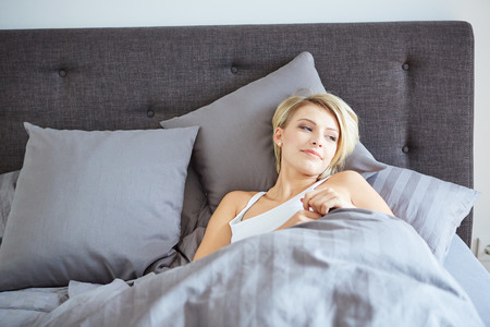 A woman resting in bed with hands beside her head on the pillow. photo