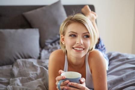 Glücklich lächelnde schöne blonde Frau mit dem Erwachen Tasse Kaffee im Schlafzimmer