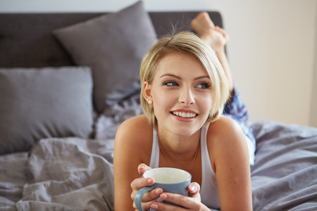 1 woman only: Happy smiling beautiful blond woman awaking with cup of coffee at bedroom