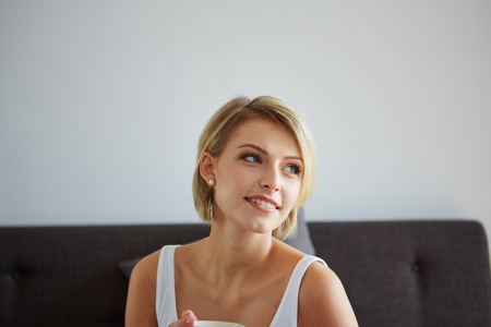 awaking: Happy smiling beautiful blond woman awaking with cup of coffee at bedroom