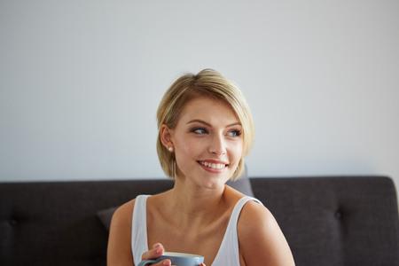 ベッドルームで、コーヒーのカップと覚醒幸せの笑みを浮かべて美しい金髪の女性