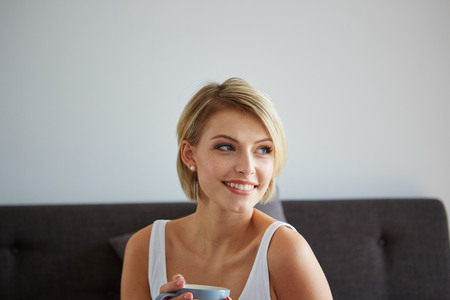 Happy smiling beautiful blond woman awaking with cup of coffee at bedroom 版權商用圖片 - 38108015