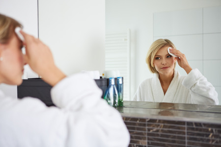 removing make up: a woman removing makeup from her face