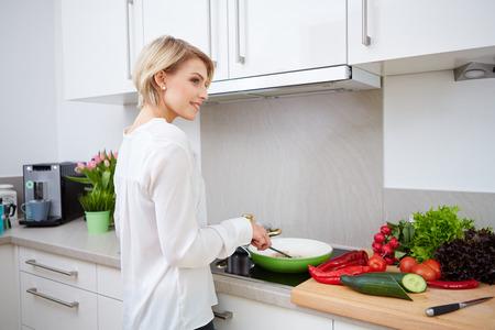 タブレット コンピューターを使用して彼女のキッチンで調理する金髪の女性