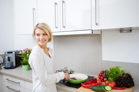 delantal: Mujer rubia con un tablet PC a cocinar en su cocina Foto de archivo