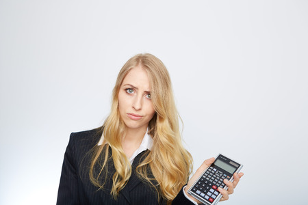 examiner: attractive smiling business woman with calculator isolated on white