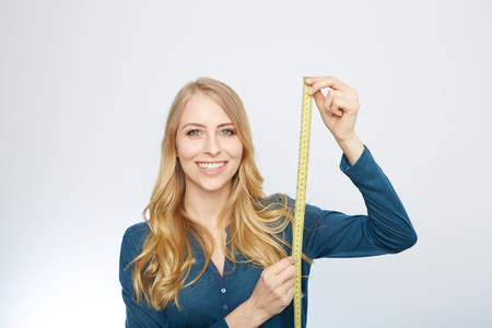 skinny girl: young woman holding a tape measure. isolated on white