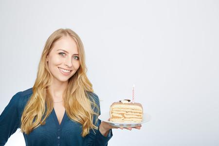 blonde yeux bleus: Les yeux bleus belle jeune femme blonde avec un gros morceau de gâteau au chocolat heureux regardant la caméra sur fond blanc portrait Banque d'images