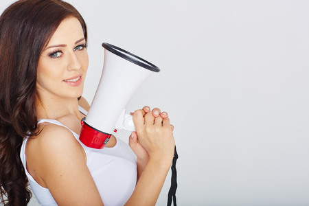 vintage pin up: Attractive brunette woman with a megaphone in studio