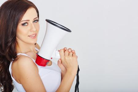 pin up vintage: Attraente donna bruna con un megafono in studio