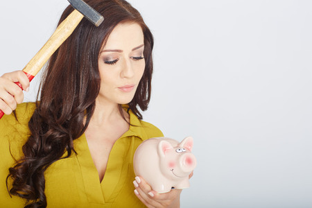 young woman smashed piggy bank with a hammer in a studio photo