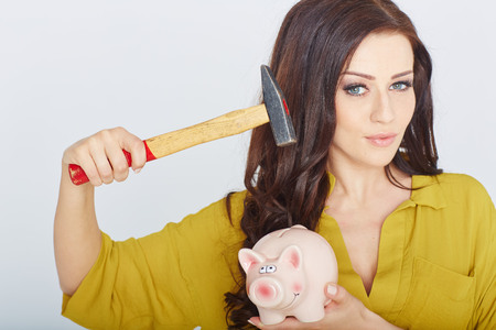 rates: young woman smashed piggy bank with a hammer in a studio