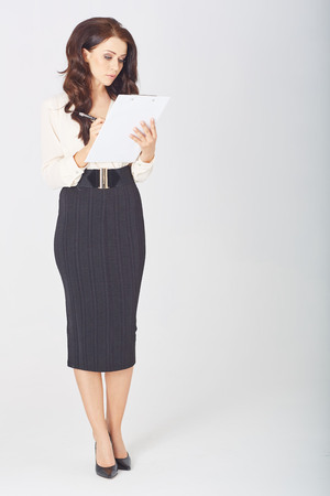 office notes: a beautiful businesswoman with a clipboard  in studio Stock Photo