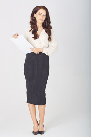 a beautiful businesswoman with a clipboard  in studio Stock Photo