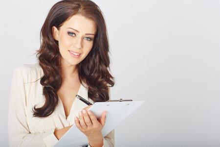 persona escribiendo: una bella mujer de negocios con un sujetapapeles en el estudio