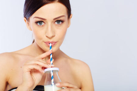 sudio: young woman with a glass of milk. in sudio