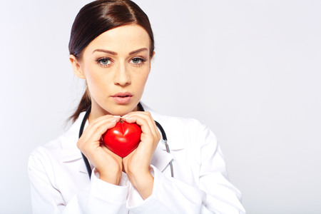 female doctor holding a heart, isolated on white background photo