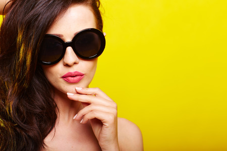 female fashion: caucasian woman wearing sunglasses over yellow background