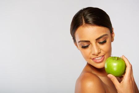 dientes sanos: Mujer sonriente con la manzana aislada en blanco