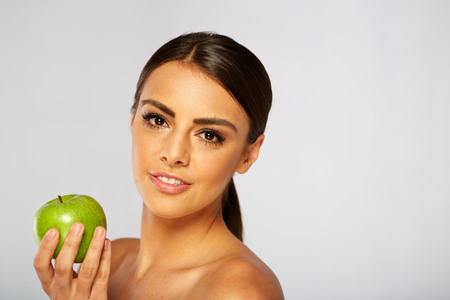 beautiful teeth: Smiling woman with apple isolated on white