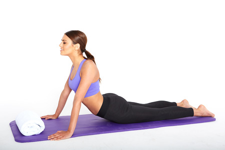 active wear: pretty brunette in active wear on white background making yoga