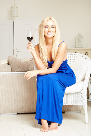 mimbre: Portrait of sexy beautiful blonde woman wearing a blue dress, sitting on wicker chair.