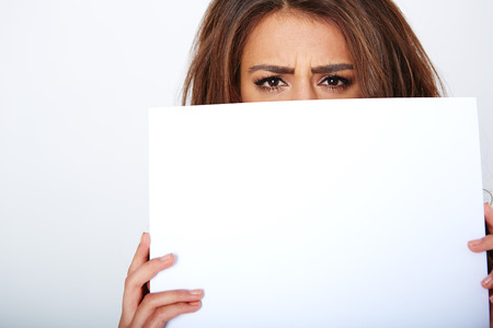 over white: Banner sign woman peeking over edge of blank empty paper billboard with copy space for text. Stock Photo