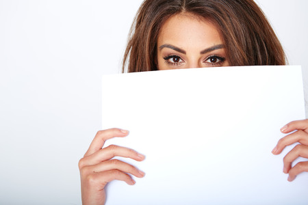 over the edge: Banner sign woman peeking over edge of blank empty paper billboard with copy space for text. Stock Photo