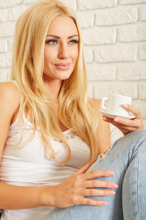 mujer elegante: Elegante hermosa mujer descalza en pantalones de mezclilla que beben el café
