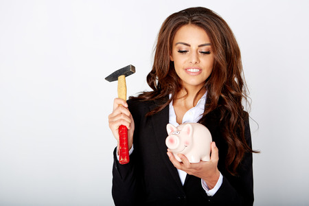 dissolve: young woman smashed piggy bank with a hammer in a studio