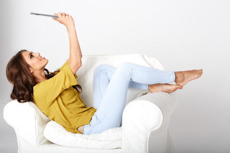 relaxing at home: Happy young woman with tablet pc laying on sofa