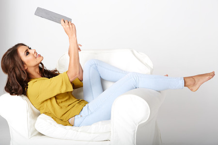 topicality: Happy young woman with tablet pc laying on sofa