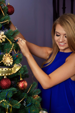 young tree: bright picture of woman decorating christmas tree Stock Photo