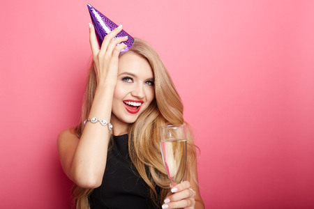 holiday celebration: Young celebrating woman black dress, holding a glass of champagne. Stock Photo
