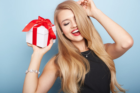 Young woman puts her ear to the present wrapped in white paper, isolated on white. Stock Photo