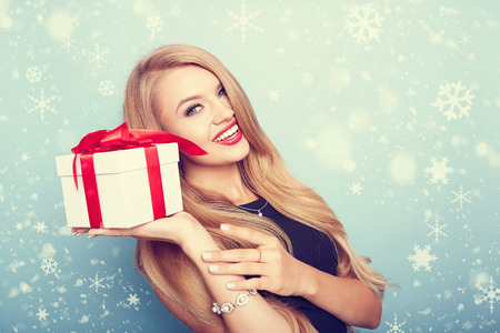winter fashion: christmas, x-mas, valentines day, celebration concept. smiling woman in red dress with gift box