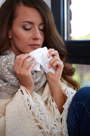 gripa: Gripe. Imagen del primer de la mujer enferma frustrado con la nariz roja