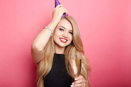 adult birthday: Young celebrating woman black dress, holding a glass of champagne. Stock Photo