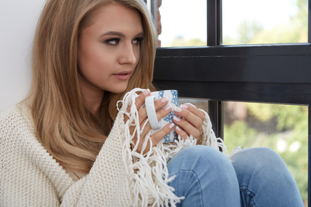 woman window: Young woman in a sweater by the window in a loft.