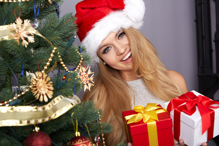 christmas present: christmas, x-mas, winter, happiness concept, smiling woman in santa helper hat with many gift boxes Stock Photo