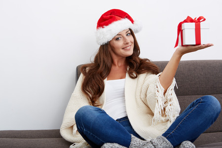 woman on couch: Christmas Santa hat isolated woman portrait hold christmas gift. Smiling happy girl on white background sitting on a couch.