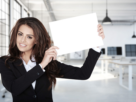 humane: Portrait of smiling  business woman with blank board , in a office. Stock Photo
