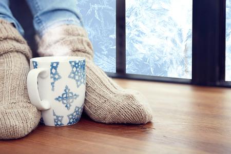 woman's feet, in woolen socks by the window. photo