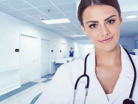 white coat: Portrait of woman doctor at hospital corridor,  looking at camera, smiling.
